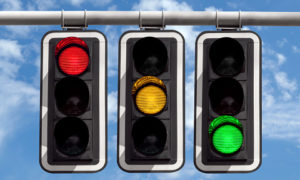 Three traffic lights against blue sky background